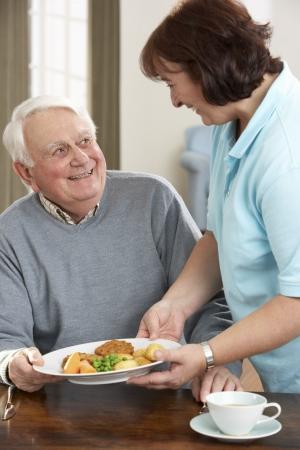 Senior hombre sirven comida por cuidador Foto de archivo