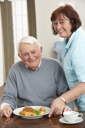 Senior hombre sirven comida por cuidador
