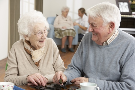 Couple Playing Dominoes At Day Care Centre Stock Photo