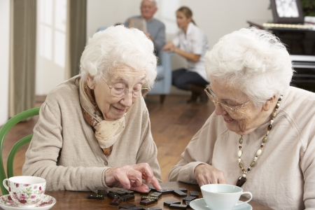 nursing home: Two Senior Women Playing Dominoes At Day Care Centre Stock Photo