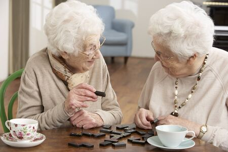 seniors homes: Two Senior Women Playing Dominoes At Day Care Centre Stock Photo