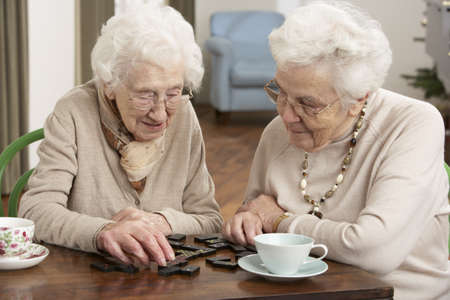 senior women: Two Senior Women Playing Dominoes At Day Care Centre Stock Photo