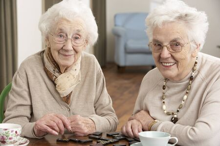 senior friends: Two Senior Women Playing Dominoes At Day Care Centre Stock Photo