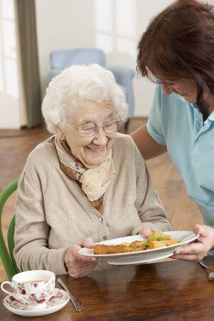 Mujer Senior sirven comida por cuidador