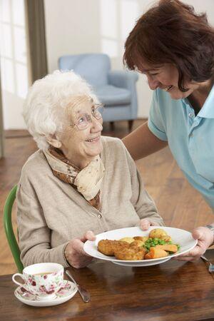 comidas: Mujer Senior sirven comida por cuidador