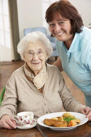 tercera edad: Mujer Senior sirven comida por cuidador