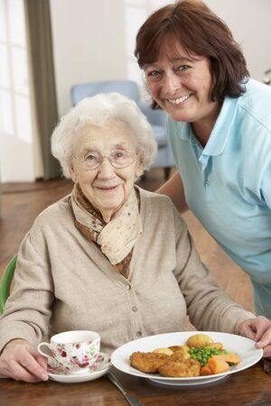 independently: Senior Woman Being Served Meal By Carer