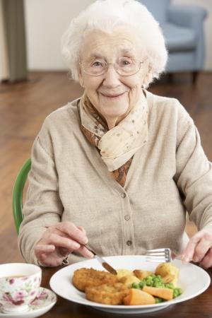 Senior vrouw genieten van de maaltijd Stockfoto