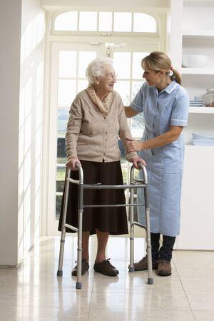 fisioterapia: Cuidador ayuda a anciana Senior utilizando marco caminando