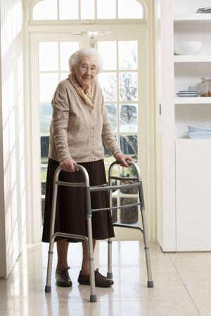 Oudere Senior vrouw met behulp van wandelen Frame