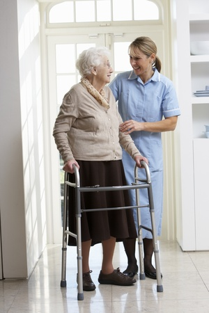 disabled person: Carer Helping Elderly Senior Woman Using Walking Frame
