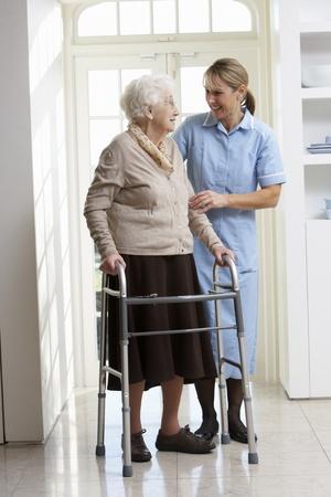 ancianos caminando: Cuidador ayuda a anciana Senior utilizando marco caminando
