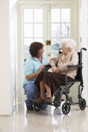 independently: Carer With Disabled Senior Woman Sitting In Wheelchair Stock Photo