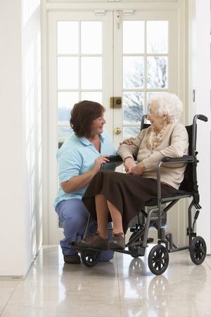 persona en silla de ruedas: Cuidador con discapacitados Senior mujer sentada en silla de ruedas