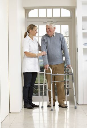 carer: Carer Helping Elderly Senior Man Using Walking Frame Stock Photo