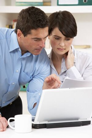 Worried Couple Working From Home Using Laptop photo