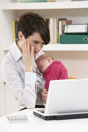 Stressed Woman With Newborn Baby Working From Home Using Laptop Stock Photo - 9911713