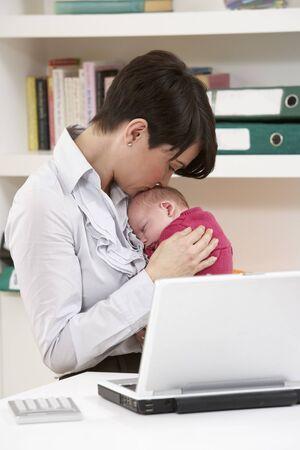 madre trabajadora: Mujer con reci�n nacido beb� trabajo desde casa utilizando port�til Foto de archivo