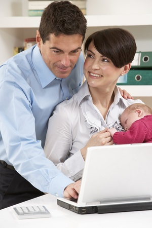 Parents With Newborn Baby Working From Home Using Laptop photo