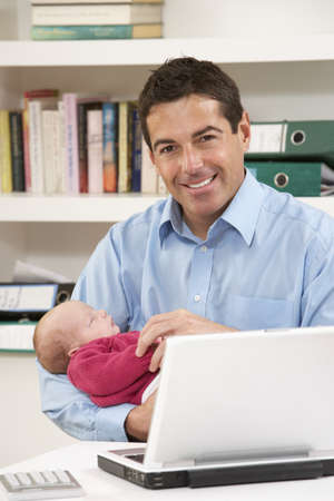 Father With Newborn Baby Working From Home Using Laptop photo