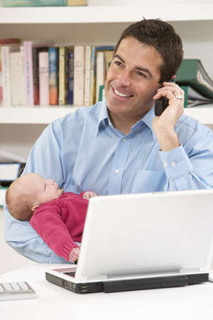 paternity: Father With Newborn Baby Working From Home Using Laptop