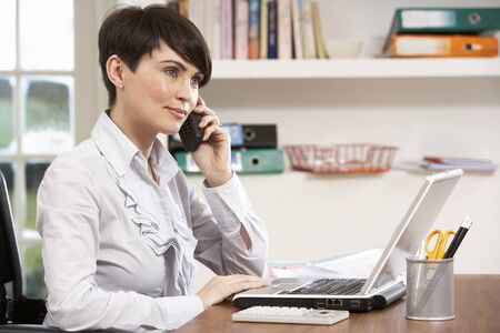 Woman Working From Home Using Laptop On Phone Stock Photo - 9911434