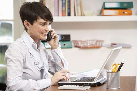 Woman Working From Home Using Laptop On Phone Stock Photo - 9911430