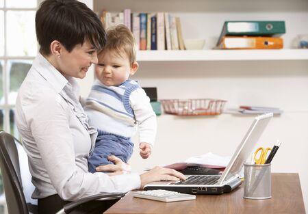 werkende moeder: Vrouw met Baby werken vanuit huis met behulp van Laptop Stockfoto