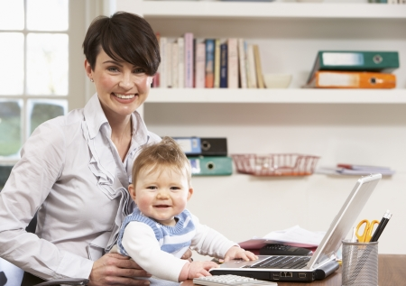Woman With Baby Working From Home Using Laptop Stock Photo - 9911583