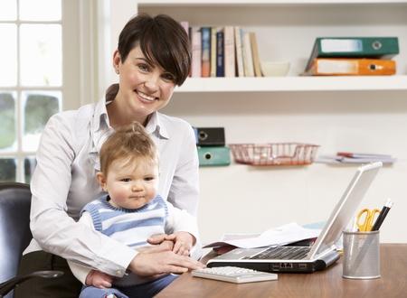 madre trabajadora: Mujer con beb� trabajo desde casa utilizando port�til