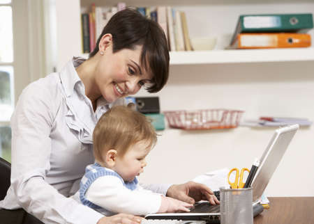 Woman With Baby Working From Home Using Laptop Stock Photo - 9911616
