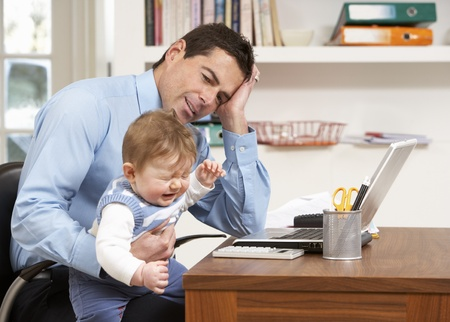 stressed businessman: Stressed Man With Baby Working From Home Using Laptop