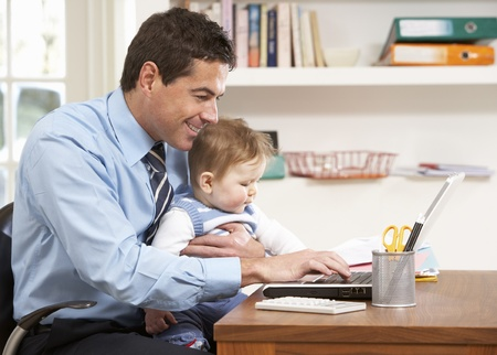 home office: Man With Baby Working From Home Using Laptop