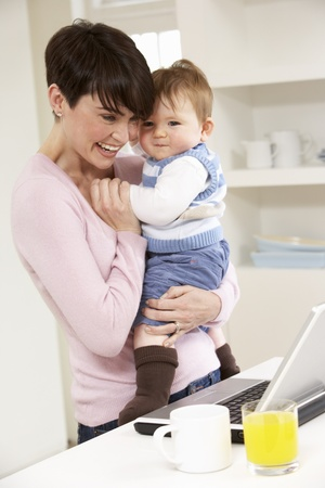 Woman With Baby Working From Home Using Laptop Stock Photo - 9911450