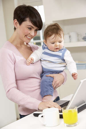Woman With Baby Working From Home Using Laptop Stock Photo - 9908783