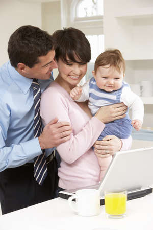 Parents With Baby Working From Home Using Laptop Stock Photo - 9908719