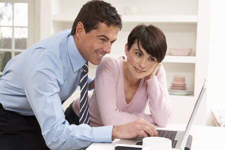 Couple Working From Home Using Laptop photo