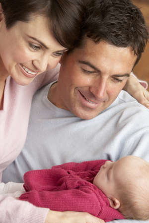 realtionship: Portrait Of Proud Parents With Newborn Baby At Home Stock Photo