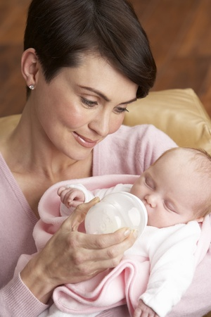 realtionship: Portrait Of Mother Feeding Newborn Baby At Home