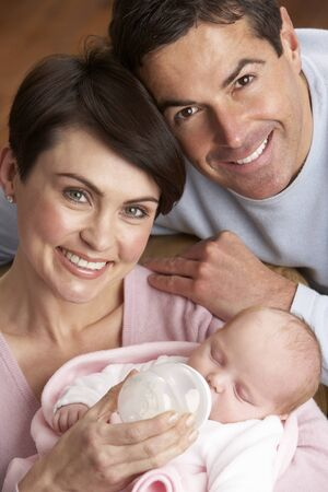Portrait Of Parents Feeding Newborn Baby At Home photo