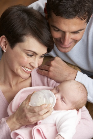Portrait Of Parents Feeding Newborn Baby At Home Stock Photo - 9908745