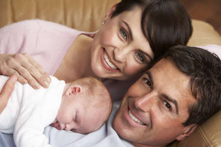 male parent: Portrait Of Proud Parents With Newborn Baby At Home Stock Photo