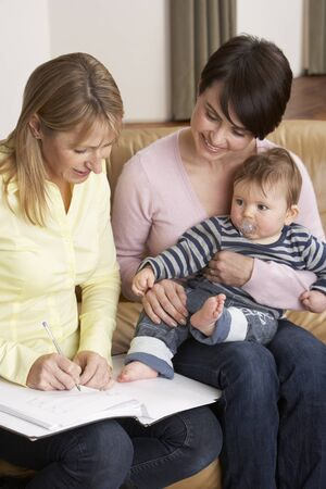 home health nurse: Mother With Baby Talking With Health Visitor At Home