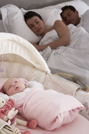 Newborn Baby Sleeping In Cot In Parents Bedroom photo