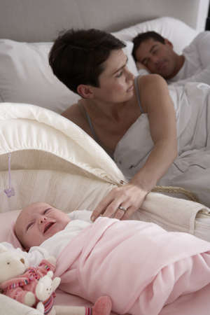 nightime: Newborn Baby Crying In Cot In Parents Bedroom Stock Photo