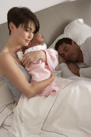 nightime: Mother Cuddling Newborn Baby In Bed At Home Stock Photo