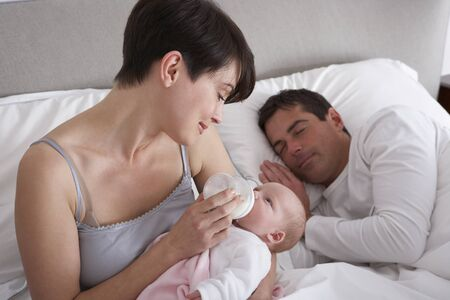 Mother Feeding Newborn Baby In Bed At Home photo