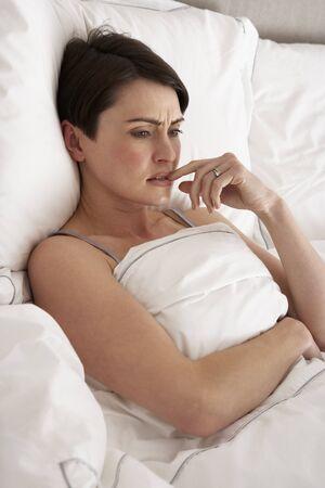 worried woman: Worried Woman Laying Awake In Bed Stock Photo