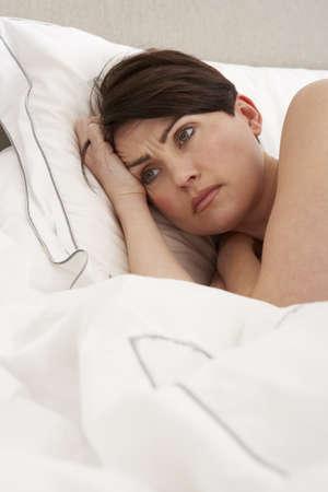despertarse: Mujer preocupada tendido despierto en la cama