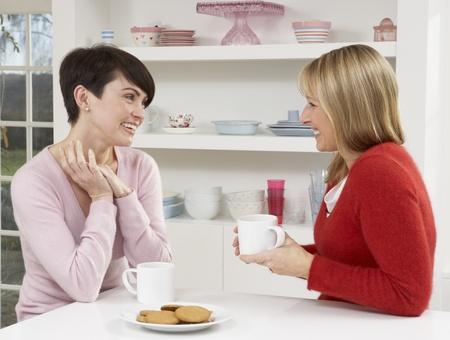 dos personas hablando: Dos mujeres disfrutando caliente bebida en cocina